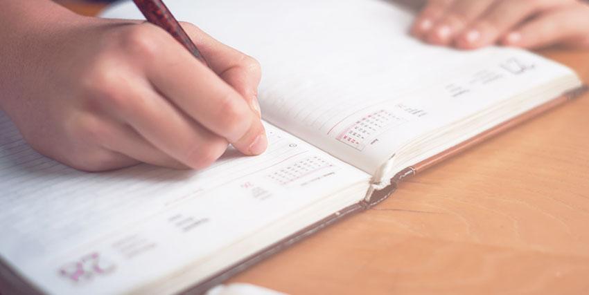 手帳にメモを書く人