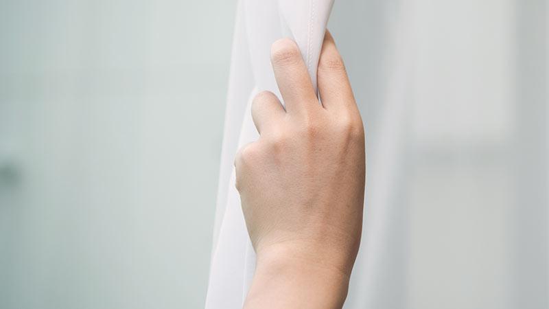 カーテンをつかむ手