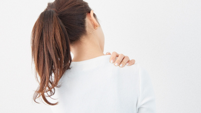 肩を触る女性