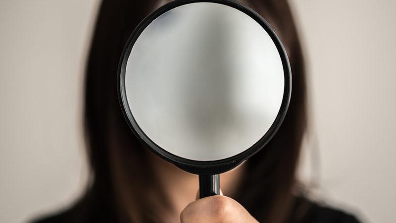 顔に鏡を当てる女性